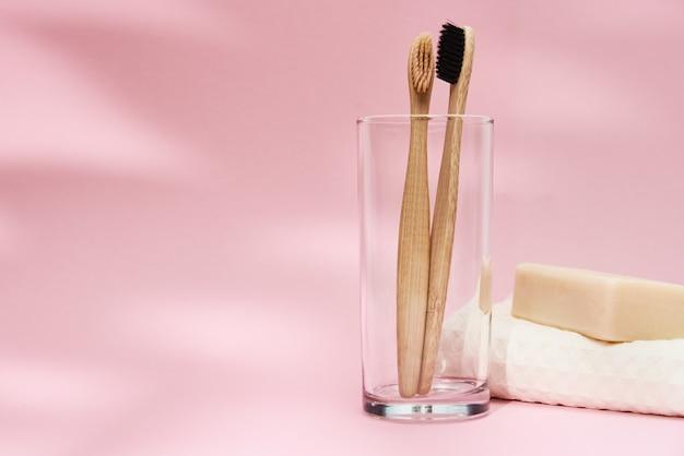 Bamboe tandenborstels in glas en bladschaduwen op roze achtergrond