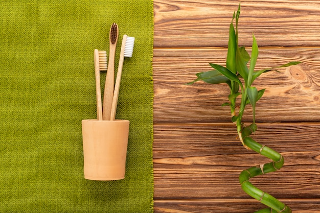Bamboe tandenborstels in klei glas bamboe plant op houten achtergrond. plat leggen geen afval