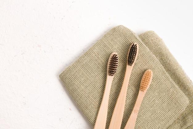 Bamboe tandenborstels op een natuurlijke stof, witte achtergrond kopie ruimte, bovenaanzicht