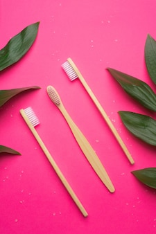 Bamboe tandenborstels op een roze achtergrond.