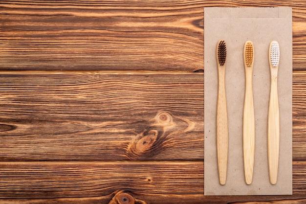 Bamboe tandenborstels op houten achtergrond. plat leggen met kopieerruimte. natuurlijke badproducten. biologisch afbreekbare tandenborstel van natuurlijk bamboe. milieuvriendelijk, geen afval, tandheelkundige zorg kunststofvrij concept.