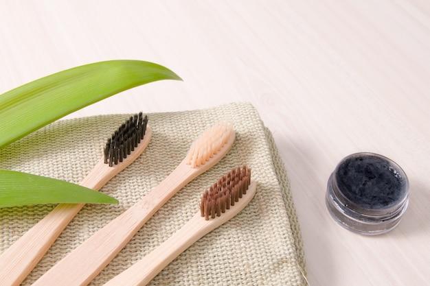 Bamboe tandenborstels op natuurlijke doek op een houten tafel, zelfgemaakte houtskool tandpasta eco-vriendelijke levensstijl concept