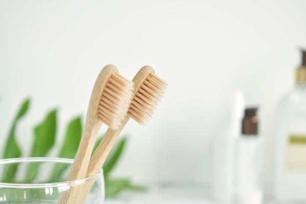 Bamboe tandenborstels zijn milieuvriendelijk in een glas met een kopie van de ruimte op een marmerwitte achtergrond. zero waste. gratis plastic.