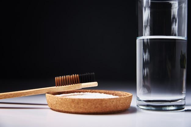 Bamboe tandenborstels, zuiveringszout en glas water op een donkere achtergrond. eco-vriendelijke tandenborstels, zero waste-concept