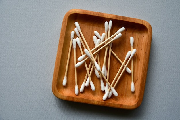Bamboe wattenstaafjes op een houten plaat. grijs papier oppervlak. geen afvalconcept. uitzicht van boven. kopieer ruimte.