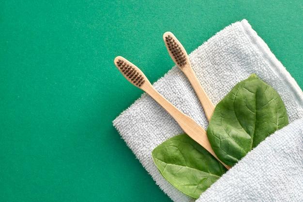 Bamboetandenborstel op handdoek met groene bladeren