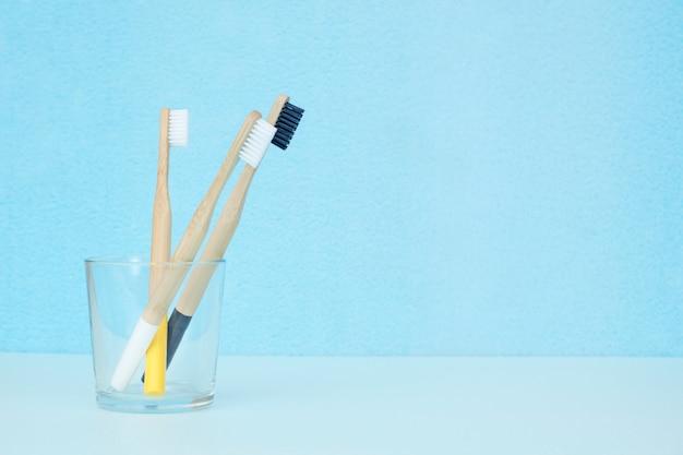 Bamboetandenborstels van verschillende kleuren in een transparant glas op een blauwe achtergrond met een exemplaarruimte. geen afvalconcept