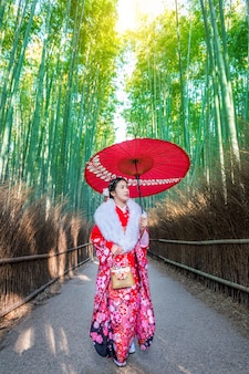 Bamboo bos. aziatische vrouw die japanse traditionele kimono draagt bij bamboo forest in kyoto, japan.