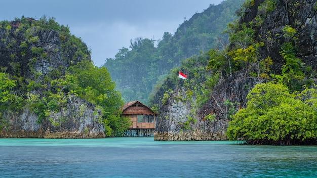 Bamboo hut tussen enkele rotsen onder regen in bay, pianemo-eilanden, raja ampat, west-papoea, indonesië