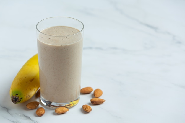 Banaan-amandel-smoothie op marmeren achtergrond