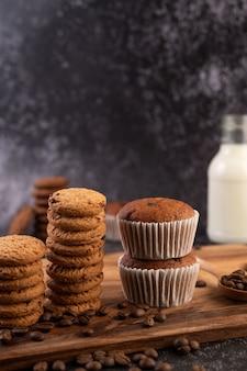 Banaan cupcakes die op een houten bord met koffiebonen worden geplaatst.