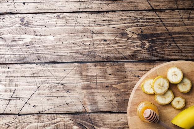 Banaan en gesneden banaan in stukjes met honing op houten tafel,