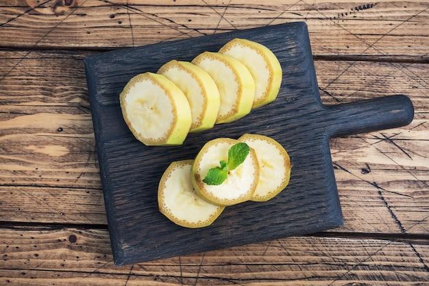 Banaan en gesneden banaan in stukjes met munt op houten rustiek. bovenaanzicht