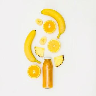 Banaan; gehalveerd oranje; plak ananas over de smoothiefles tegen witte achtergrond