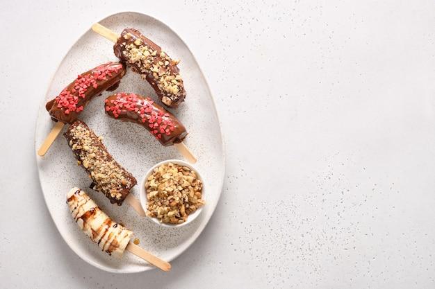 Banaan lollies met walnoten en rode harten hagelslag.
