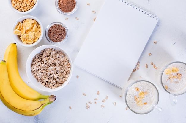 Banaan smoothie in kopjes, lijnzaad, cacao, havermout en gepofte rijst op een witte achtergrond. gezond eten concept