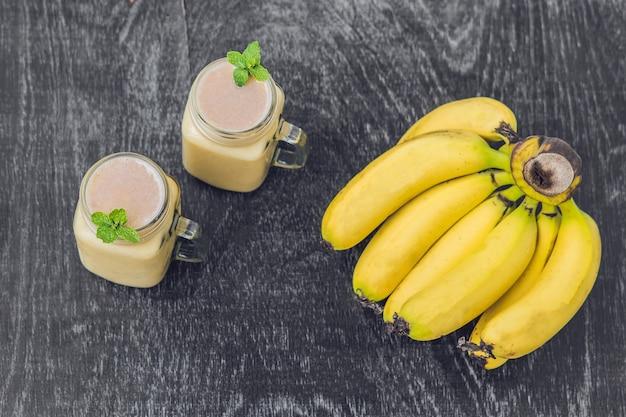 Banaan smoothies en bananen op een oude houten achtergrond.