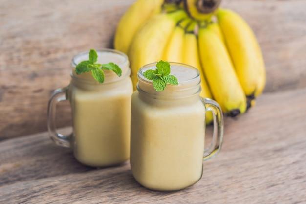 Banaan smoothies en bananen op een oude houten