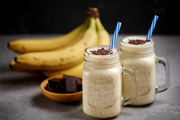 Banaanmilkshake in een glas met chocolade op grijze concrete oppervlakte, close-up