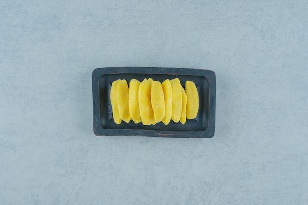 Banaanvormige kauwsnoepjes in een houten plank op een witte ondergrond