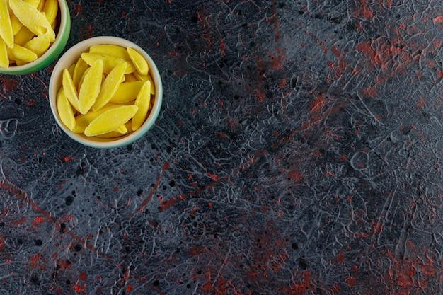 Banaanvormige kauwsnoepjes op een donkere tafel.