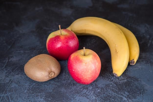 Bananen, appels en kiwi op de achtergrond van een donkere tafel. gezonde levensstijl. vegetarisch eten. gezond eten