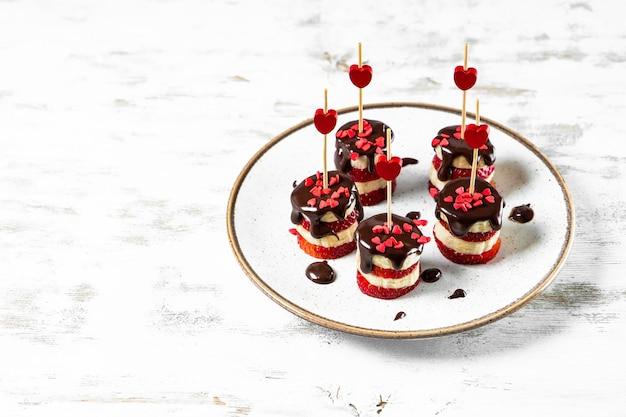 Bananen- en aardbeienhapjes in chocoladeglazuur op een witte plaat, een origineel voorgerecht voor valentijnsdag, vrije ruimte voor uw tekst. hoge kwaliteit foto