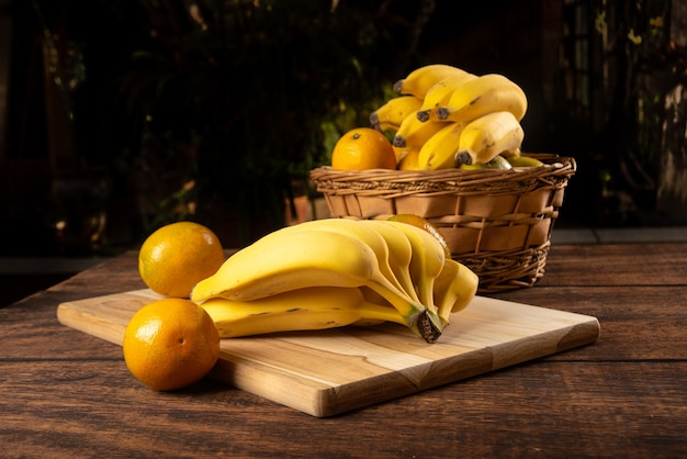 Bananen en sinaasappelen op gepolijst hout, geplaatst op rustiek hout met selectieve aandacht.
