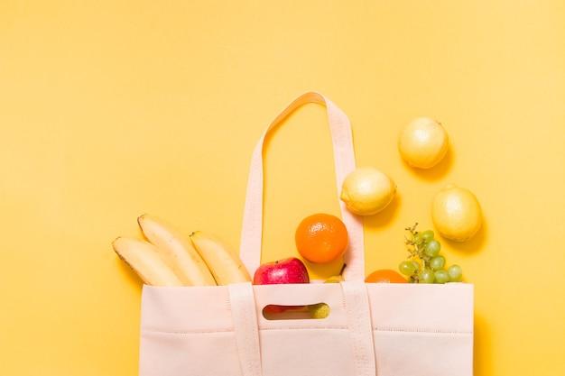 Bananen, mandarijnen, druiven, appel, peer en citroenen in een stoffen boodschappentas op geel oppervlak