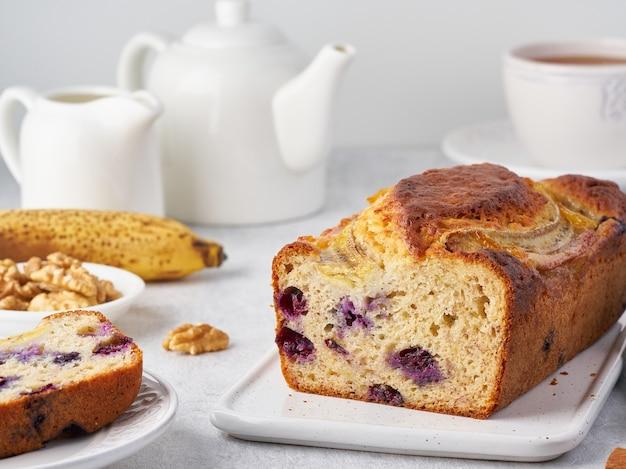 Bananenbrood, gesneden cake met banaan en bosbessen. ochtendontbijt met thee op lichtgrijze concrete achtergrond. zijaanzicht.