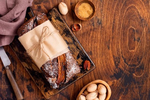Bananenbrood met kaneelkrokant en bestrooid met poedersuiker op lichte betonnen tafel.