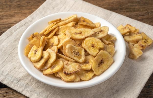 Bananenchips in een witte plaat op een linnen servet. zijaanzicht. gezonde snoepjes.