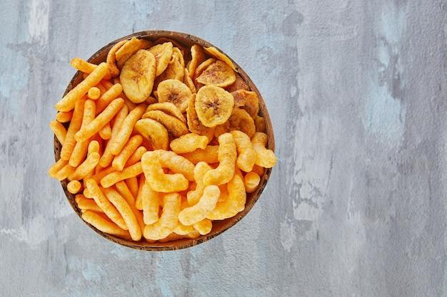 Bananenchips zijn een gezonde maaltijd en gekruide maïssnacks zijn een geweldige snack in een kom.