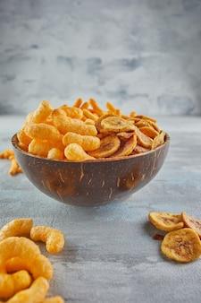 Bananenchips zijn een gezonde maaltijd en gekruide maïssnacks zijn een geweldige snack in een kom. Premium Foto