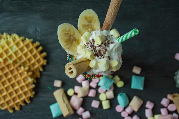Bananenmilkshake met ijs en slagroom, marshmallows, koekjes, wafels, geserveerd in een glazen beker.