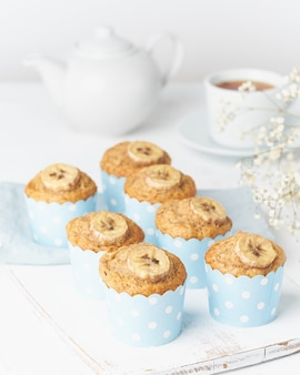 Bananenmuffin, cupcakes in blauw cakevormend document, witte concrete lijst