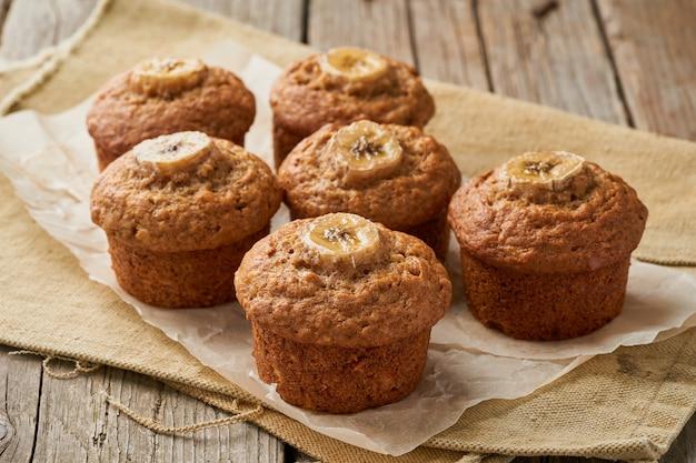 Bananenmuffin, zijaanzicht. cupcakes op oud linnenservet, rustieke houten lijst, ontbijt met cake