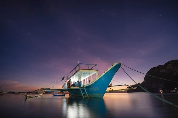Banca-boot binnen na zonsonderganglandschap in de lagune van el nido, palawan-eiland, filippijnen.