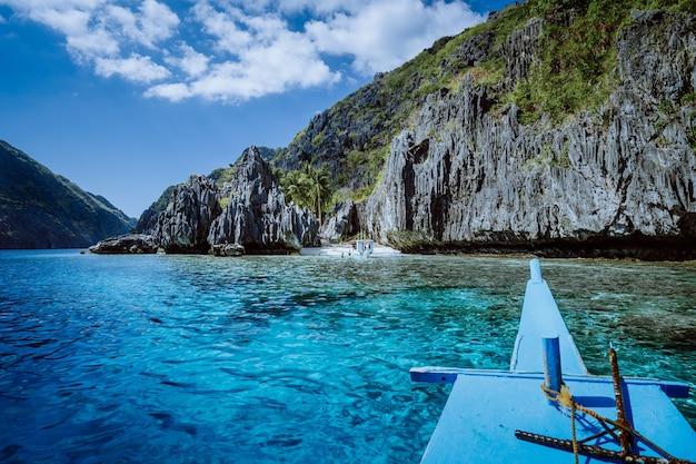 Banca-boot nadert het kleine strand bij het heiligdom, op het eiland matinloc, hoogtepunten van de hoptrip tour c. moet je zien, de mooiste plek in het marine national park, palawan.