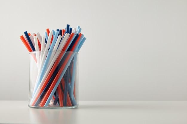 Banch van pastel levendig gekleurd dik rietje in transparante glazen pot geïsoleerd op een witte tafel