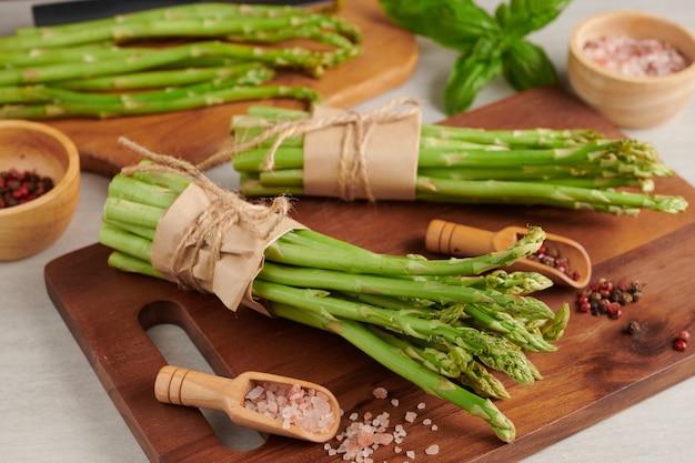 Banches van verse groene asperges op houten oppervlak