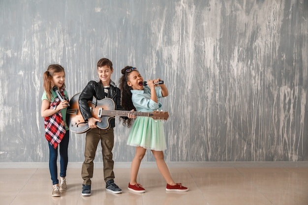 Band van kleine muzikanten tegen grungemuur