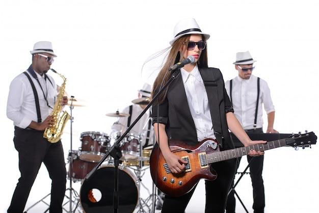 Band van muzikanten met instrumenten in witte kamer.