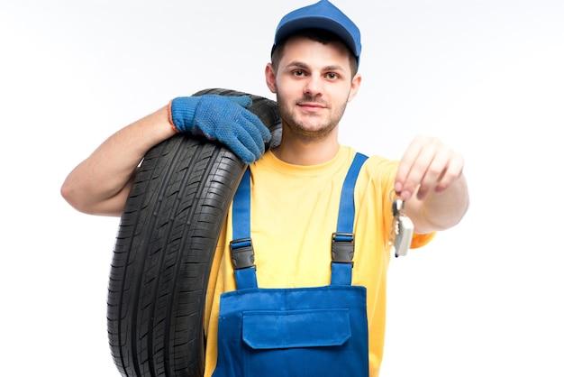 Bandenservice, werknemer in blauw uniform houdt band en autosleutels in handen, wit, reparateur, wielmontage