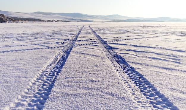Bandensporen in de sneeuw op het ijsoppervlak van het baikalmeer