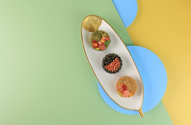 Bandung, indonesië, 02092021: drie zelfgemaakte maancake (mooncake) op mint gele achtergrond. concept voor mid autumn festival met kopie ruimte voor tekst