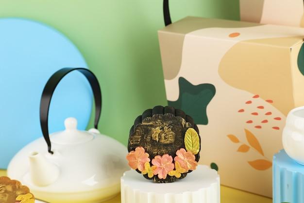 Bandung, indonesië, 02092021: zelfgemaakte premium black moon cake (mooncake) met gouden stof geïsoleerd op zwarte achtergrond. concept voor mid autumn festival