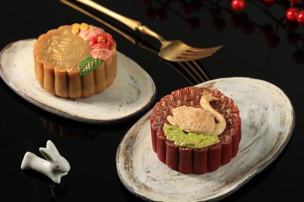 Bandung, indonesië, 02092021: zelfgemaakte premium moon cake (mooncake) met gouden stof geïsoleerd op zwarte achtergrond. concept voor mid autumn festival met kopie ruimte voor tekst