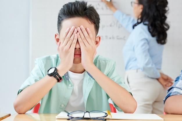 Bang aziatische schooljongen die gezicht bedekt met handen wanneer wiskundeleraar lange vergelijking op whiteboard schrijft