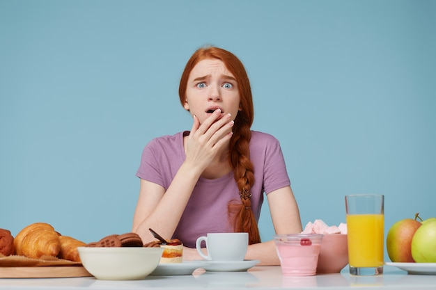 Bang bang roodharig meisje bedekt open mond met een handpalm, zit aan een tafel waarop veel verschillende soorten voedsel staan